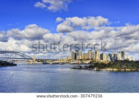 Australian capital city Sydney landmarks from Balls Head reserve on bright sunny day across blue still waters of Harbour with bridge and CBD skyscrapers over horizon - stock photo