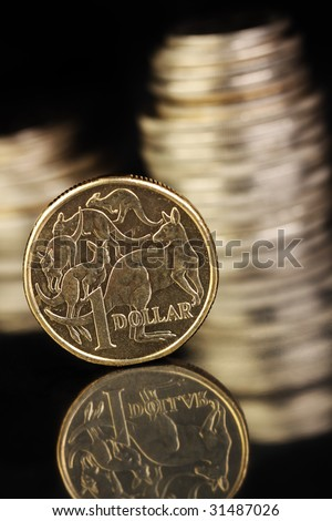 Australian $1coin on a dark reflective surface. Various aussie coins in the background. - stock photo