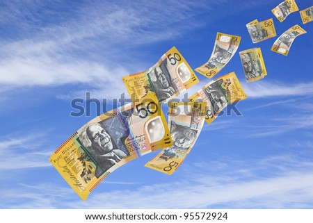 Australian fifty dollar bills falling from a blue sky. - stock photo