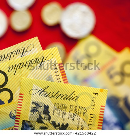 Australian fifty dollar notes over red background.  Blurred coins and notes behind. - stock photo
