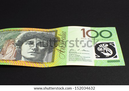 Australian green and gold  100 hundred dollar note, against a black background, laying flat. - stock photo