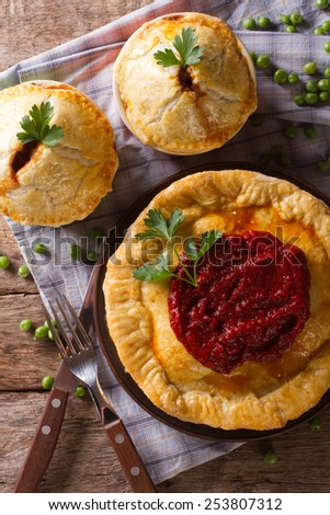 Australian meat pie on the table, a vertical top view, rustic style  - stock photo