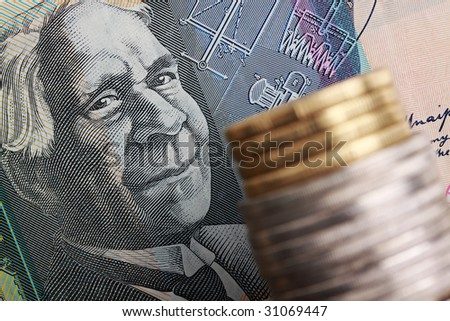 Australian $50 note with coins stacked in foreground. Focus on face of David Unaipon, aboriginal writer and inventor. - stock photo