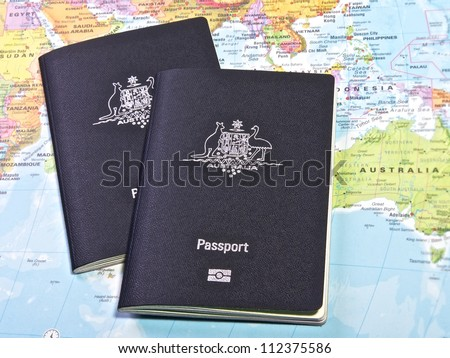 Australian Passport with the world map in the background - stock photo
