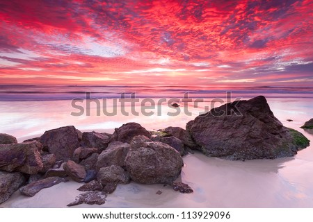 australian seascape at sunrise with rich in red color cloud formation - stock photo