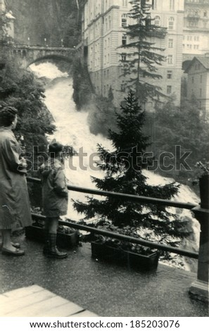 AUSTRIA, BAD GASTEIN - CIRCA 1958: An antique photo of woman and boy on the observation deck watching a torrent mountain Wrekin background multi-storey building - stock photo