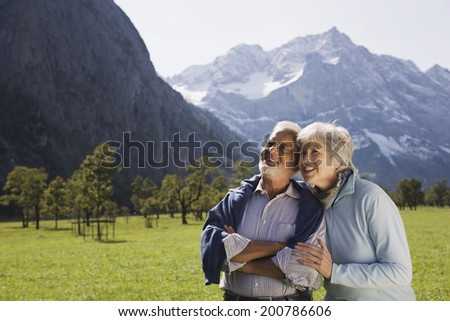Austria, Karwendel, Ahornboden, senior couple embracing in mountain scenery - stock photo