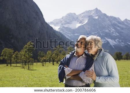 Austria, Karwendel, Ahornboden, senior couple embracing in mountain scenery - stock photo