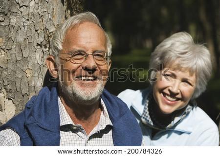 Austria Karwendel senior couple man leaning on tree trunk woman behind smiling close up - stock photo