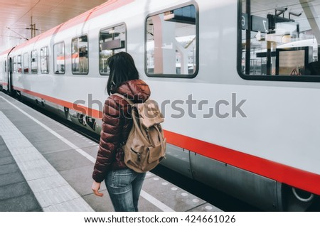AUSTRIA, SALZBURG - APRIL 21, 2016: Girl standing on the platform at the train wagon. Traveling by train at the Alpine Railroad.