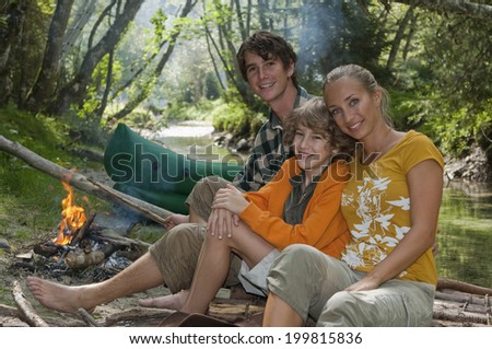 Austria, Salzburger Land, Family sitting at campfire, smiling - stock photo