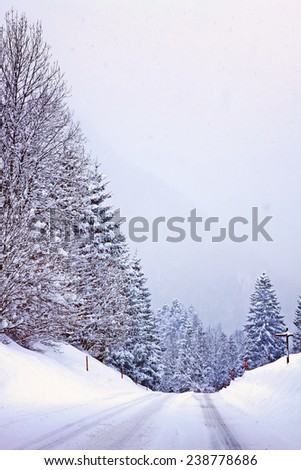 Austrian Alpine route on winter time during snowfall, Instagram-like vintage filter added. - stock photo
