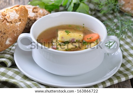Austrian clear broth with salted sponge mixture, so called 'schoeberl', made of baked eggs and butter with ham or bacon