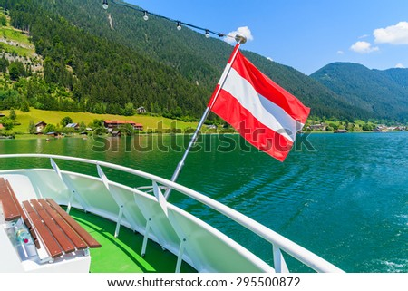 Austrian flag waving on the wind during ship cruise on green water Weissensee lake, Austria - stock photo