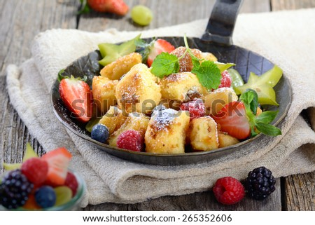 Austrian 'Kaiserschmarrn' (like shredded sweet pancakes) served with fresh colorful fruit in an iron pan on vintage linen - stock photo