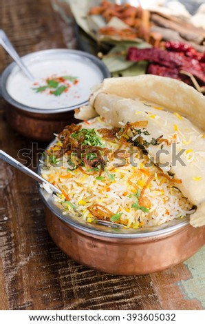 Authentic chicken biryani served with naan bread, fragrant pilau rice and yoghurt, in a metal pot. - stock photo