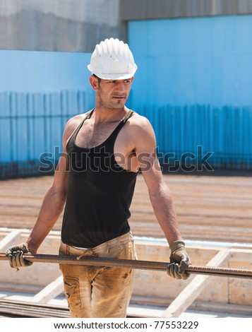 Authentic construction worker carrying reinforcement steel bars in construction site - stock photo
