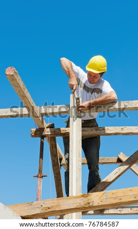 Authentic construction worker on scaffold, hammering nails on the wooden formwork of a construction site - stock photo