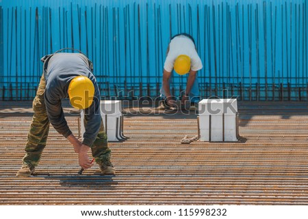 Authentic construction workers installing binding wires to reinforcement steel bars in front of a blue insulated surface prior to pouring concrete - stock photo