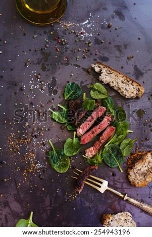 Authentic grilled fillet steak served with herbs on a old vintage metal table in a country kitchen. Concept image for healthy cooking. Moody lighting, rustic and natural atmosphere. See series. - stock photo