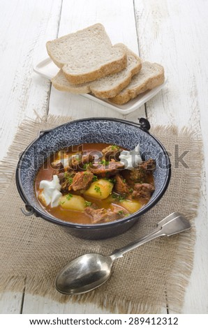 authentic hungarian goulash in a kettle with bell pepper, potato, carrot, sour cream and bread on a plate - stock photo