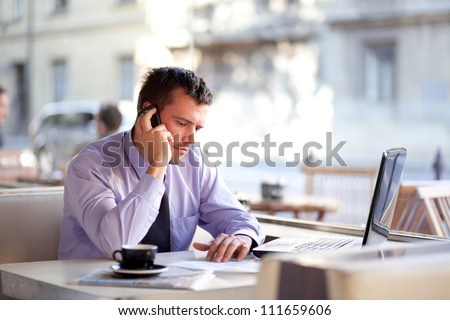 Authentic image of a businessman working in a coffee shop - stock photo