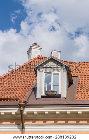 Authentic mansard window in a old style tiled roof - stock photo