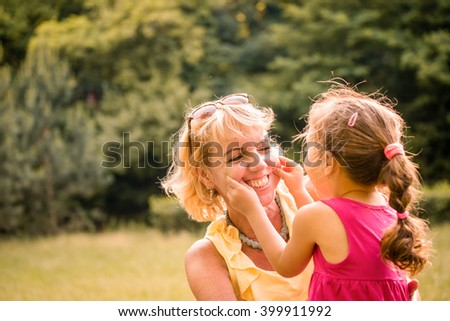 Authentic photo of grandmother and her grandchild playing together and having fun outdoor in nature - stock photo