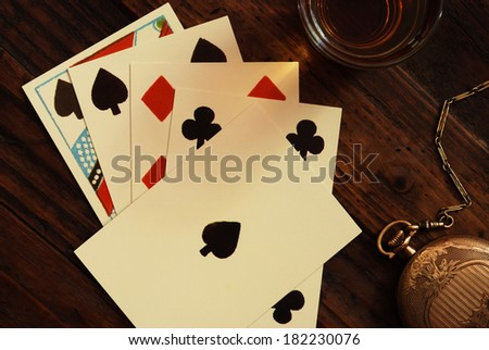 Authentic reproduction Civil War playing cards with antique pocket watch and shot of whiskey on rustic wood background.  Closeup taken from above with directional lighting for effect.   - stock photo