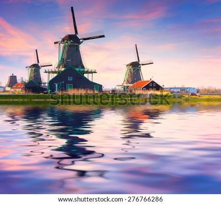 Authentic Zaandam mills on the water channel in Zaanstad village. Zaanse Schans Windmills and famous Netherlands canals, Europe. - stock photo