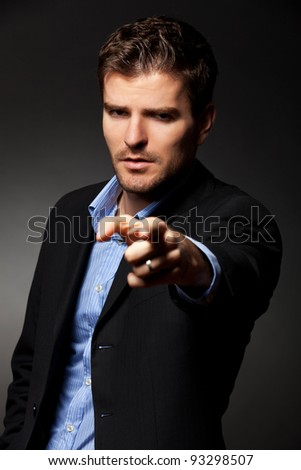 Authoritative, serious business man pointing accusing finger to someone
