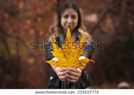 Autmn girl holds the dry leave. Caucasian woman smiling happy on cloudy autmn day outside in woods. - stock photo