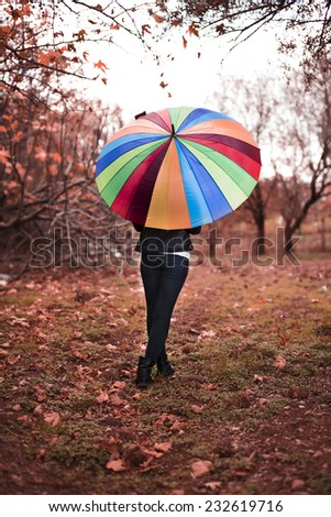 Autmn girl portrait with a rainbow umbrella. Caucasian woman smiling happy on cloudy autmn day outside in woods - stock photo