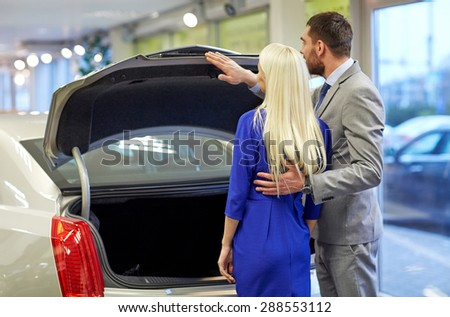 auto business, car sale and people concept - happy couple choosing car in auto show or salon - stock photo