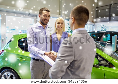 auto business, car sale and people concept - happy couple with dealer shaking hands in auto show or salon over snow effect