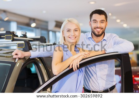 auto business, car sale, consumerism and people concept - happy couple buying car in auto show or salon - stock photo