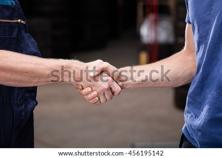 Auto business, car sale, deal, gesture and people concept - close up of men shaking hands in car service salon.
