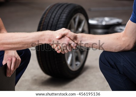 Auto business, car sale, deal, gesture and people concept - close up of men shaking hands with car tire background in car service salon. - stock photo