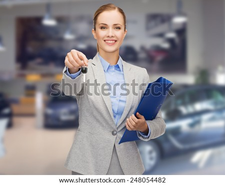 auto business, car sale, gesture and people concept - happy businesswoman or saleswoman with folder giving car key over auto show background - stock photo