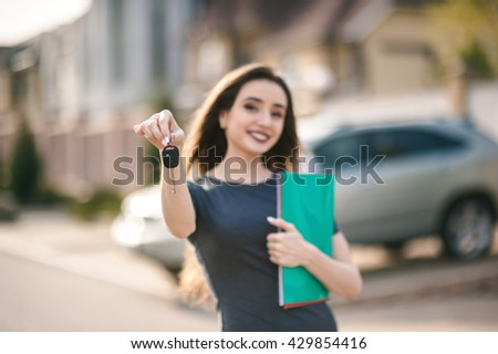 auto business, car sale, gesture and people concept - happy businesswoman or saleswoman with folder giving car key over auto background