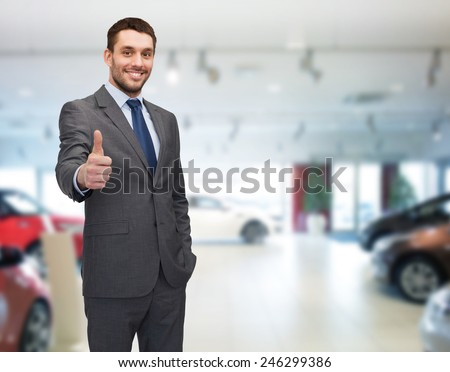 auto business, car sale, gesture and people concept - smiling businessman showing thumbs up over auto show background - stock photo