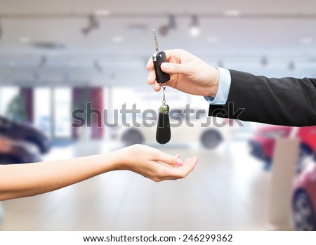 auto business, car sale, transportation, people and ownership concept - close up of car salesman giving key to new owner or customer over auto show background - stock photo