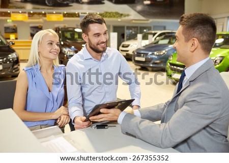auto business, sale and people concept - happy couple with dealer buying car in auto show or salon - stock photo