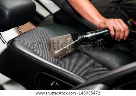 Auto car service cleaning the drivers seat, cleaning and vacuuming leather - stock photo