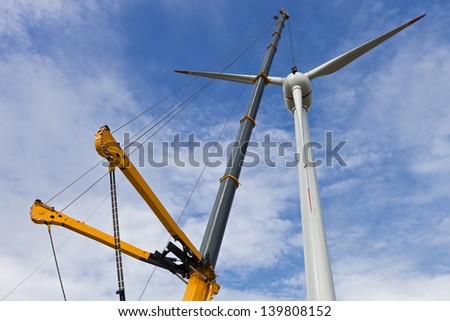 Auto-crane lifting propeller for windmill - stock photo