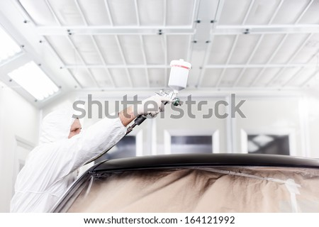 Auto engineer painting a black car in special garage and wearing protective gear - stock photo