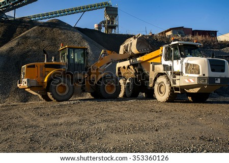 Auto loader is unloading scoop with gravel into dump truck. - stock photo