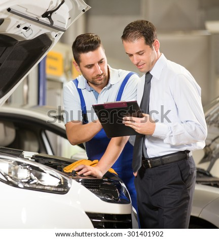 Auto mechanic and technician working in repair shop. - stock photo