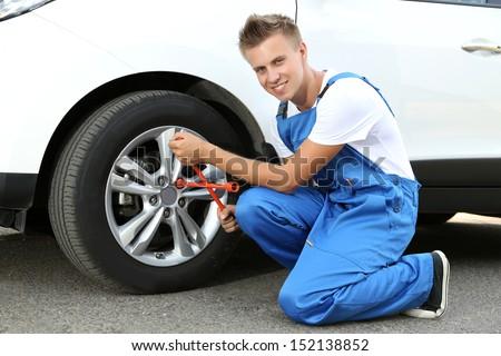 Auto mechanic changing wheel - stock photo