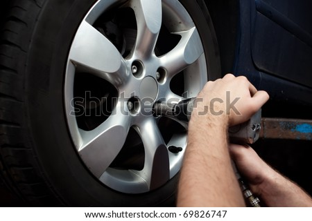 Auto mechanic changing wheel on car with pneumatic wrench.